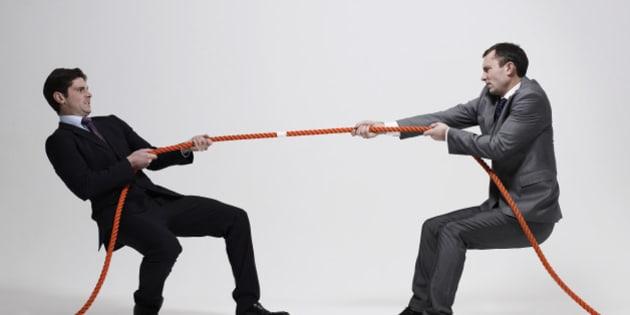 Businessmen playing tug-of-war