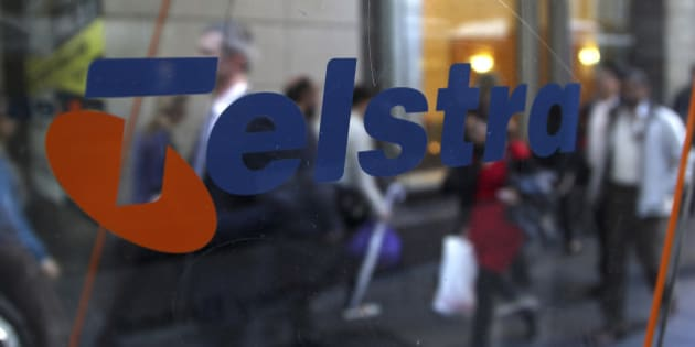 Business people walk through the foyer of Telstra Corp.'s head office in Sydney, Australia, Thursday, Aug. 9, 2012.  Australia's largest telecommunications company reported a 5.4 percent increase in annual profit amid a boost in new mobile phone customers. (AP Photo/Rob Griffith)