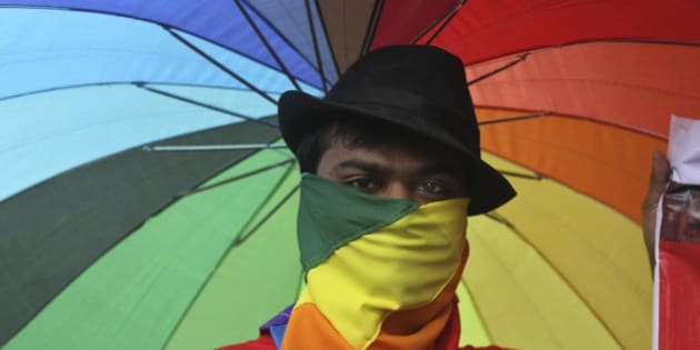 A participant holds an umbrella with rainbow colors as members of the Lesbian, Gay, Bisexual, Transgender (LGBT) community and their supporters from across India participate in a pride walk in Surat in Gujarat state, India, Sunday, Oct. 6, 2013. The walk was organized for the first time in the Gujarat state demanding social acceptance and equal rights. (AP Photo/Ajit Solanki)