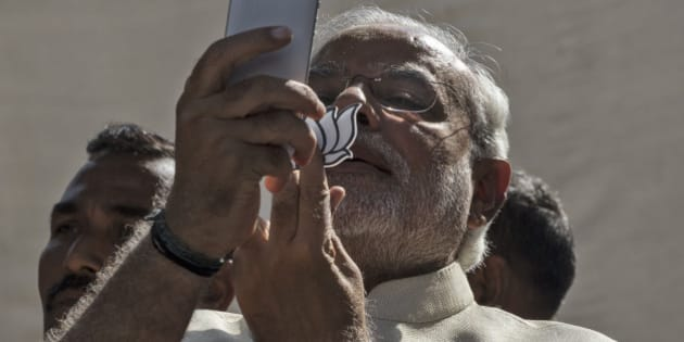AHMEDABAD, INDIA - APRIL 30:  BJP leader Narendra Modi takes a picture of himslef, his inked finger and the party insignia with his mobile phone after voting at a polling station on April 30, 2014 in Ahmedabad, India. India is in the midst of a nine-phase election that started on April 7 and ends May 12.  (Photo by Kevin Frayer/Getty Images)