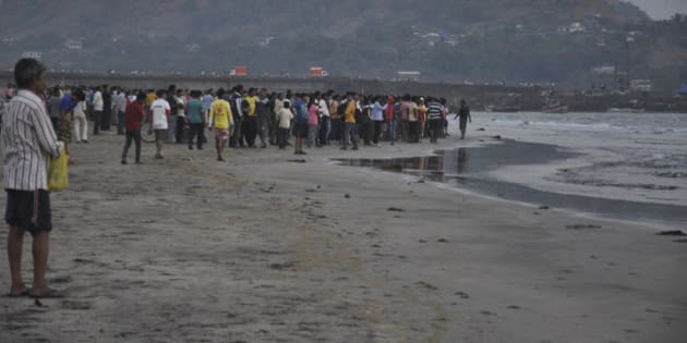 People gather on the beach after more than a dozen college students were swept away at Murud on the Arabian Sea coast about 150 kilometers (95 miles) south of Mumbai, Maharashtra state, India, Monday, Feb. 1, 2016. Police say the students who were on a school picnic have drowned while swimming in the sea in western India. (AP Photo/Sudhir Nazare)