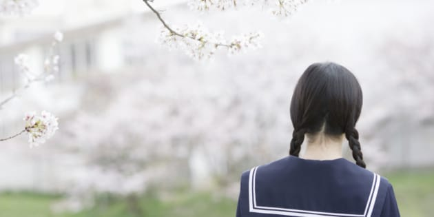 Teenage girl in school uniform standing by cherry tree, rear view