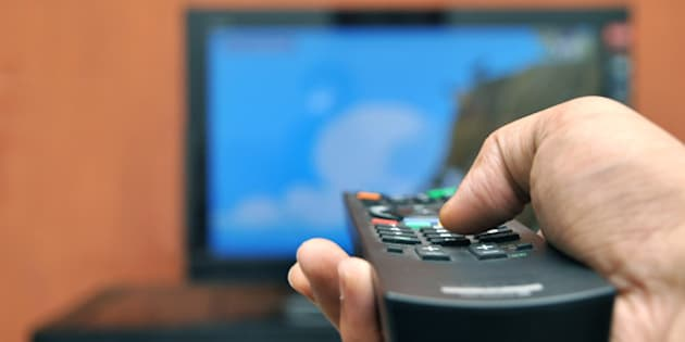 A man holding a TV remote control.