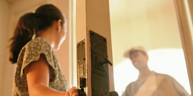 Man delivering package, woman standing in doorway (Enhancement)