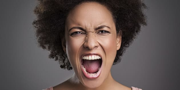 Young African woman shouting angrily.