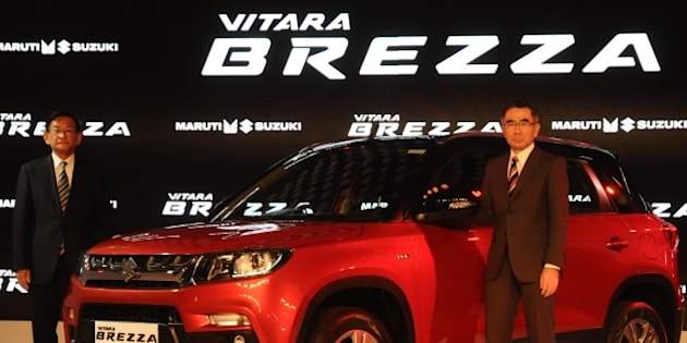 DELHI, INDIA - FEBRUARY 3: Suzuki Motors President Toshihiro Suzuki (R) and Kenichi Ayukawa, Managing Director and CEO of Maruti Suzuki India Ltd., pose with their newly launched Brezza car during the Indian Auto Expo in Greater Noida, on the outskirts of  Delhi , February 03, 2016.   (Photo by Imtiyaz Khan/Anadolu Agency/Getty Images)