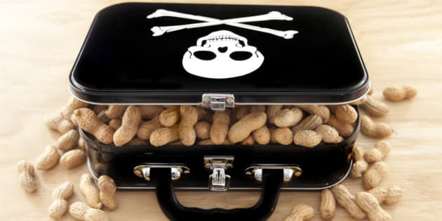 Black lunchbox with skull and crossbones on lid and peanuts overflowing out of container