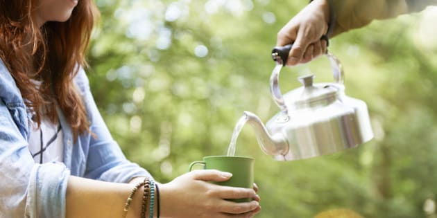 woman holding cup of tea in forest