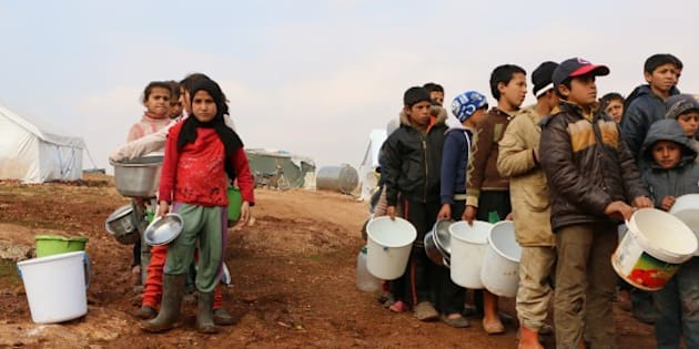 ALEPPO, SYRIA - JANUARY 31:  Turkmen children carry wait for food distribution at al-Ra'ee camp, southern Aleppo in Syria on January 31, 2016. Turkmen who fled their homes following attacks by Syrian and Russian forces, live under harsh conditions at al-Ra'ee camp. (Photo by Mustafa Sultan/Anadolu Agency/Getty Images)