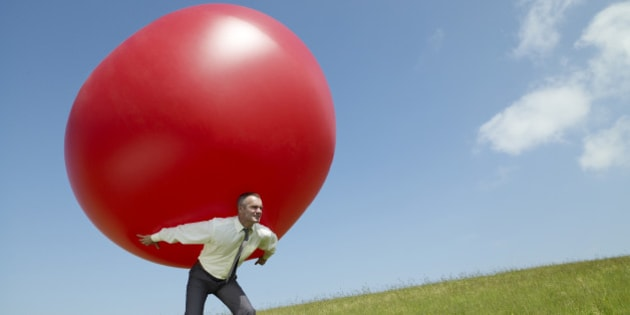 Businessman carrying large ball up a hill