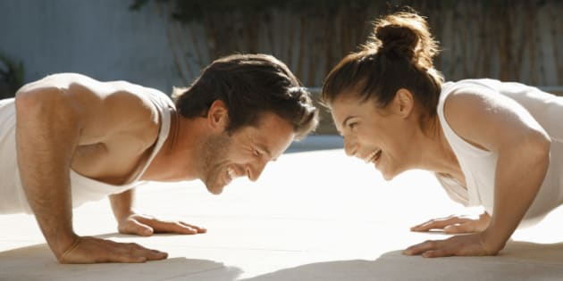 Man and woman laughing while doing push-ups