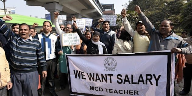NEW DELHI, INDIA - FEBRUARY 3: Delhi MCD sanitation employees and MCD teachers shout slogans against the Delhi Government and Central Government from Nirman Vihar Metro Station to ITO near Delhi Secretariat for not being paid their salaries for the last three months, on February 3, 2016 in New Delhi, India. The agitating MCD staffs on Wednesday refused to call off their strike even as the mayors of the north and east Delhi municipal corporations said that they will accept the loan extended by the AAP government as a grant only. (Photo by Sonu Mehta/Hindustan Times via Getty Images)