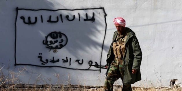 A Kurdish fighter walks by a wall bearing a drawing of the flag of the Islamic State (IS) group in the northern Iraqi town of Sinjar, in the Nineveh Province, on November 13, 2015. Iraqi Kurdish leader Massud Barzani announced the 'liberation' of Sinjar from the Islamic State group in an assault backed by US-led strikes that cut a key jihadist supply line with Syria. AFP PHOTO / SAFIN HAMED / AFP / SAFIN HAMED        (Photo credit should read SAFIN HAMED/AFP/Getty Images)