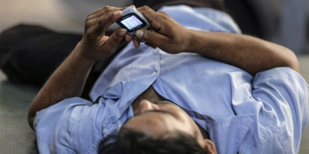 A man uses a mobile phone as he reclines in Mumbai, India, on Monday, Oct. 19, 2015. Telecom operators were allowed to trade wireless airwaves with rivals in September by the government if they were acquired through an auction since 2010 or the holder paid market value initially. Photographer: Dhiraj Singh/Bloomberg via Getty Images