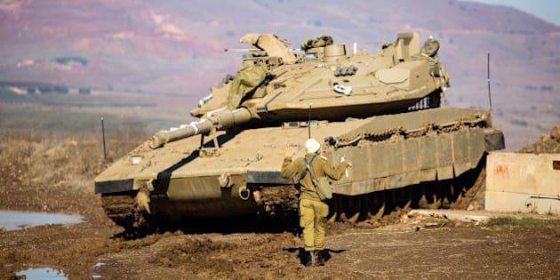 A soldier from the IDF's Artillery Corps prepares a Merkava tank on Israel's border with Syria in the Golan Heights. The army position is located on the border with the Syrian town of al-Quneitra where Bashar al-Assad, ISIS, and Syrian rebels have been in a constant battle over the territory. Israel has experienced sporadic fire and shelling from the conflict in Syria. Mt. Hermon can be seen in the background of the image.