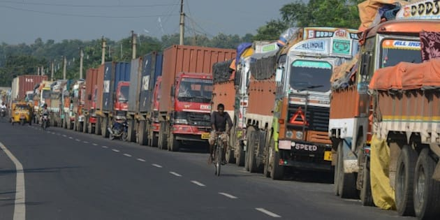 An Indian man cycles past parked Indian trucks carrying goods to Nepal near the India-Nepal border at Panitanki, some 40 kms from Siliguri on September 29, 2015. Nepal's new constitution was meant to end centuries of inequality, but instead it has sparked deadly protests and a trade blockade by ethnic minorities that has forced nationwide fuel rationing. More than 40 people have been killed in clashes between police and protesters representing ethnic minorities who say a new federal structure laid out in the constitution will leave them under-represented in the national parliament. AFP PHOTO / Diptendu DUTTA        (Photo credit should read DIPTENDU DUTTA/AFP/Getty Images)