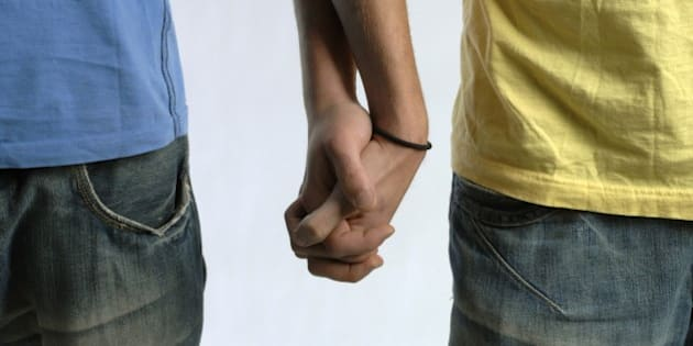 Two men holding hands, mid section