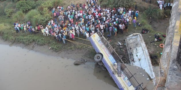 Indian rescue workers and villagers try to extract the injured and dead passengers from a Gujarat State Road Transport Corporation's passenger bus which plunged in to river Purna near Navsari, some 315 kms from Ahmedabad on February 5, 2016.  packed passenger bus plunged off a bridge into a river in western India Friday killing at least 37 people, an official said, in one of the deadliest road accidents in recent years. / AFP / STR        (Photo credit should read STR/AFP/Getty Images)