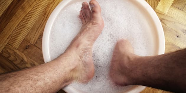 Man soaking his feet in a washbowl.