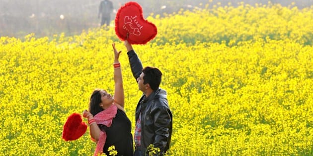CHANDIGARH, INDIA - FEBRUARY 14: A young couple sharing a light moment in an open field on the outskirts of Chandigarh as they celebrated Valentine's Day, on February 14, 2015 in Chandigarh, India. Valentine's Day, also known as Saint Valentine's Day or the Feast of Saint Valentine, is a celebration observed on February 14 each year. It is celebrated in many countries around the world, although it is not a public holiday in most of them. (Photo by Keshav Singh/Hindustan Times via Getty Images)