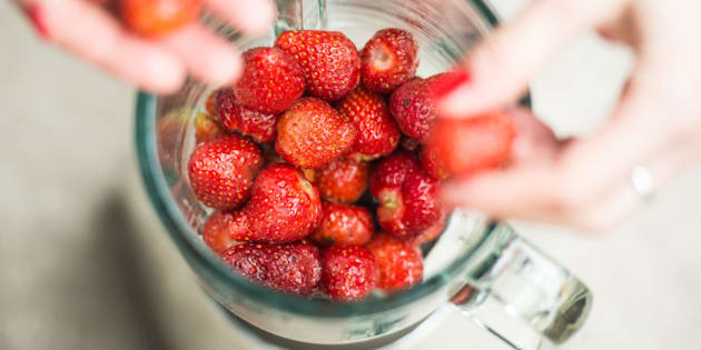 Fresh strawberries putting in blender cup and hands with some berries are blurry.