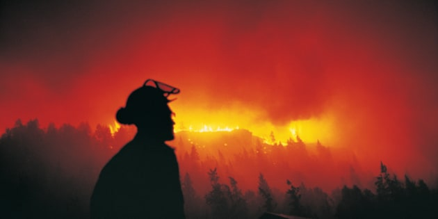 Firefighter Looking at a Forest Fire at Night