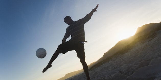 Man playing soccer on the beach, Cape Town, Western Cape Province, South Africa