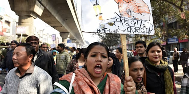 NEW DELHI, INDIA - FEBRUARY 3: Delhi MCD sanitation employees and MCD teachers shout slogans against the Delhi Government and Central Government during protest march from Nirman Vihar Metro Station to ITO near Delhi Secretariat for not being paid their salaries for the last three months, on February 3, 2016 in New Delhi, India. The agitating MCD staffs on Wednesday refused to call off their strike even as the mayors of the north and east Delhi municipal corporations said that they will accept the loan extended by the AAP government as a grant only. (Photo by Sonu Mehta/Hindustan Times via Getty Images)