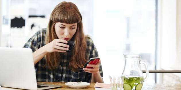Girl drinking coffee checking her phone