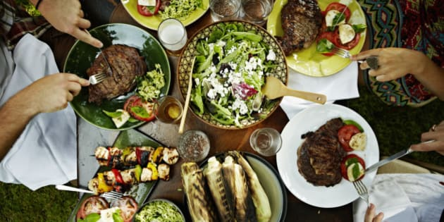 Overhead view of friends dining at table with food in backyard garden