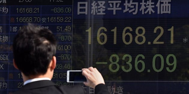 A businessman uses his smartphone to take pictures of an electric quotation board flashing the Nikkei key index of the Tokyo Stock Exchange (TSE) in front of a securities company in Tokyo on February 9, 2016. Tokyo shares tumbled nearly five percent, extending a global sell-off as a stronger yen dented exporters and after oil prices tanked again on fears of a deepening economic slowdown.     AFP PHOTO/Toru YAMANAKA / AFP / TORU YAMANAKA        (Photo credit should read TORU YAMANAKA/AFP/Getty Images)
