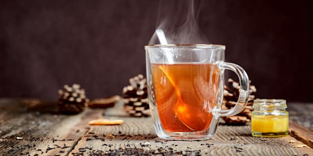 Hot black tea with steam and a little honey pot on a wooden table