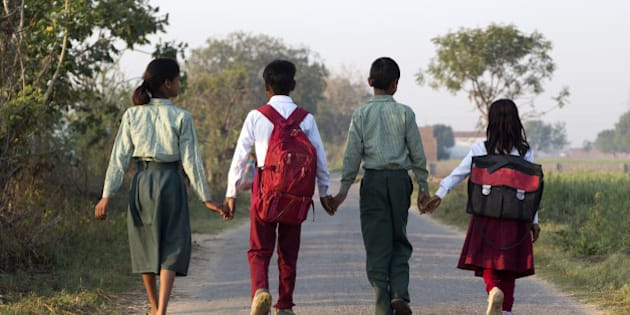 India, Uttar Pradesh, Agra, four young children walking to school hand in hand, back to camera.