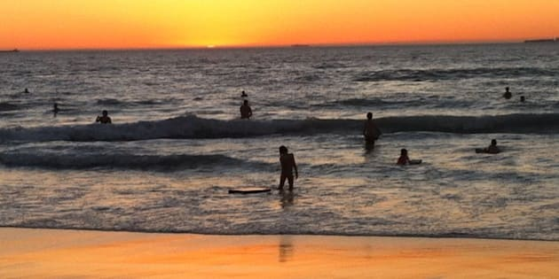 Swimmers and bodyboarders enjoy the water late at dusk during a Perth summer heatwave.