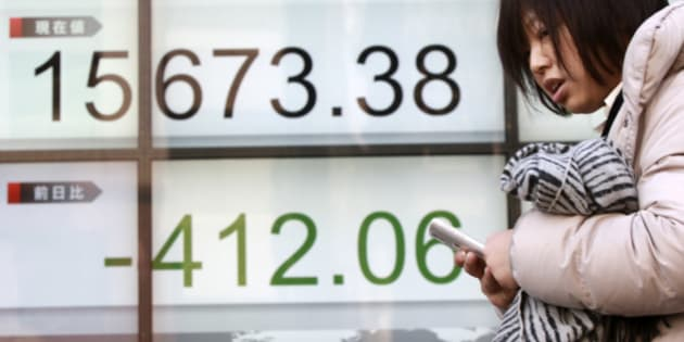 A woman walks past an electronic stock board showing Japan's Nikkei 225 in Tokyo, Wednesday, Feb. 10, 2016. Asian stock markets fell for a third consecutive day Wednesday, beset by nerves about shaky global growth, falling oil prices and possible capital shortfalls at major European banks. (AP Photo/Eugene Hoshiko)