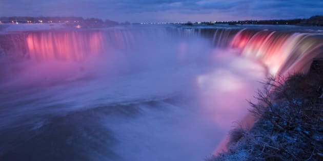 Niagra Falls Is Lit Up At Night As Seen From Canada