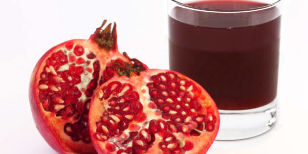 Glass of fresh pomegranate juice with ripe pomegranate cut into two halves, on a white background.
