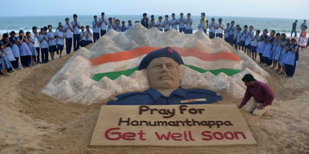 Indian students stand and pray near a sand sculpture created by Sudarsan Pattnaik of Hanumanthappa Koppad, rescued alive five days after being buried in an avalanche in the Himalayas, at Puri beach, some 65 km from Bhubaneswar, on February 10, 2016. An Indian soldier's condition deteriorated February 10, two days after his dramatic rescue from under mounds of snow nearly a week after being buried alive in an avalanche, the army said.  AFP PHOTO/ASIT KUMAR / AFP / ASIT KUMAR        (Photo credit should read ASIT KUMAR/AFP/Getty Images)