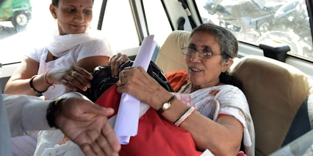 Indian Prime Minister Narendra Modi's wife, Jashodaben (R) holds a copy of the Right To Information (RTI) application filed by her as she leaves the Deputy Superintendent of Police (DSP) office in Mehsana, some 70 kms from Ahmedabad on November 24, 2014.  An RTI application requesting an explanation of the sort of government security she receives, has been filed by retired school-teacher, Jashodaben.  AFP PHOTO / Sam PANTHAKY        (Photo credit should read SAM PANTHAKY/AFP/Getty Images)