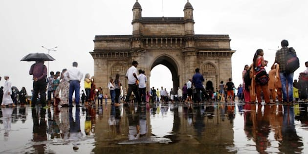 MUMBAI, INDIA - JULY 29: People enjoy after heavy rain at Gateway of India on July 29, 2015 in Mumbai, India. Heavy rains caused major waterlogging in many areas, leaving residents and commuters stranded, and causing a huge traffic gridlock. Waterlogging in many areas has led BEST to divert bus routes and trains being stalled as tracks are under water. The temperature here dropped to 28.5 degrees Celsius due to the rain, according to the weather department. (Photo by Arijit Sen/Hindustan Times via Getty Images)