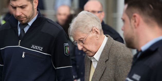 94-year-old former SS guard at the Auschwitz death camp Reinhold Hanning, center, leaves the building after the opening of his trial in Detmold, Germany, Thursday, Feb. 11, 2016. Hanning faces trial for 170,000 counts of accessory to murder, the first of up to four cases being brought to court this year in an 11th-hour push by German prosecutors to punish Nazi war crimes. (Bernd Thissen/Pool Photo via AP)