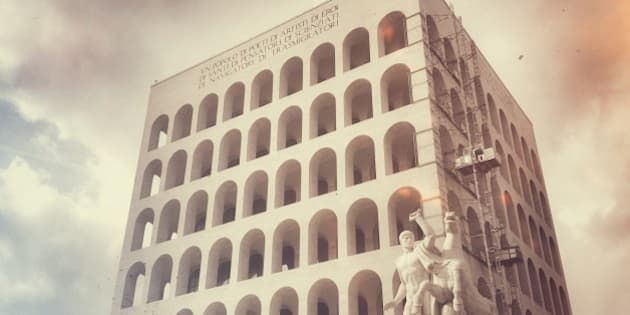 """The Palazzo della Civiltà Italiana, also known as the Palazzo della Civiltà del Lavoro or simply the Colosseo Quadrato (Square Colosseum), is an icon of Fascist architecture.   The EUR provides a large-scale image of how urban Italy might have looked if the fascist regime had not fallen during the war—large, symmetrical streets and austere buildings of limestone, tuff and marble, in either stile Littorio, inspired by ancient Roman architecture, or Rationalism. Its architectural style is often called simplified neoclassicism. Marcello Piacentini, the coordinator of the commission for E42, based it on the Italian Rationalism of Pagano, Libera, and Michelucci.  The design of the """"Square Colosseum"""" was inspired more to celebrate the Colosseum, and the structure was intended by Benito Mussolini as a celebration of the older Roman landmark. Similar to the Colosseum, the palace has a series of superimposed loggias, shown on the façade as six rows of nine arches each. These numbers are said to be an allusion to the name of the Fascist dictator: """"Benito"""" having six letters and """"Mussolini,"""" nine.[by whom?]  The palace is entirely clad in travertine marble, as is characteristic of buildings in the EUR. It is a parallelepiped on a square base, with six levels rising above a podium. The scale is imposing: the base covers an area of 8,400 square meters, and the building has volume 205,000 cubic meters with a height 68 meters (50 meters from the base)."""