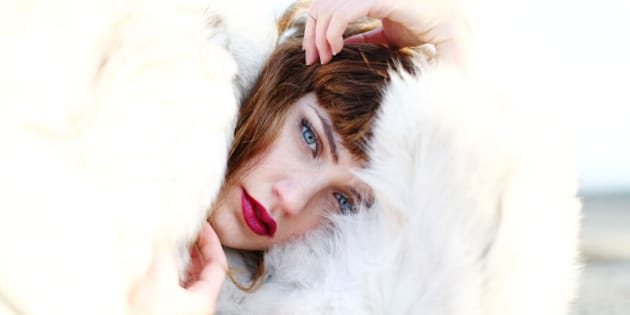 A model in a white fur coat poses during a photo shoot on a rooftop.