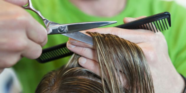 Male hairdresser cutting woman's hair short whilst holding comb, close-up