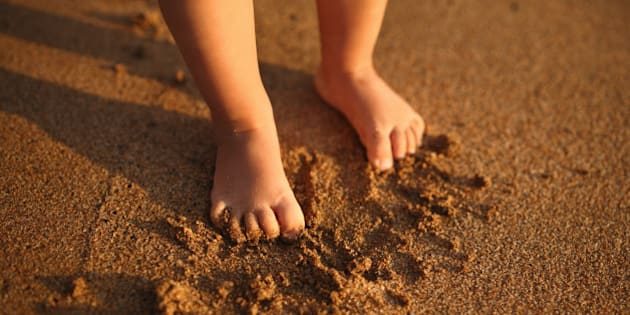Small feets of child on sandy beach