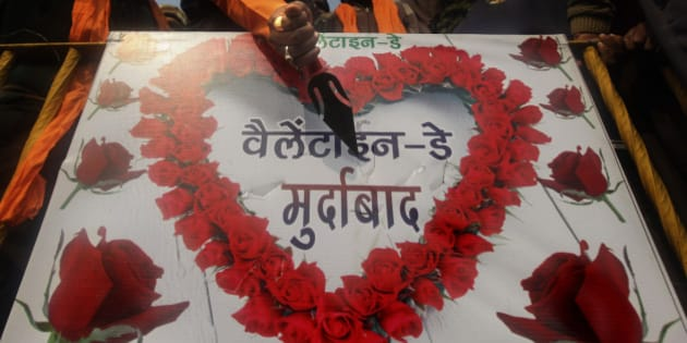 "An activist of right wing Shiv Sena pokes a knife into a placard with an anti-valentine's day message during a protest in Amritsar, India, Monday, Feb. 13, 2012. Protests by groups like Shiv Sena which says it is defending traditional Indian values from Western promiscuity have become an annual event during Valentine's Day which falls on Feb.14.  The placard in Hindi reads ""Down with Valentine's Day"". (AP Photo/Altaf Qadri)"