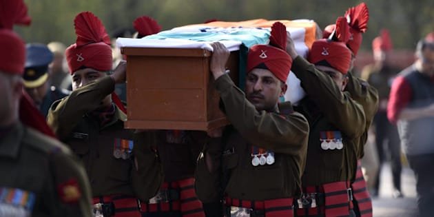 Indian soldiers carry a coffin with the body of avalanche survivor Hanumanthappa Koppad in New Delhi on February 11, 2016. Indian army soldier Koppad, who was rescued nearly a week after being buried in eight metres (25 feet) of snow by a deadly Himalayan avalanche, died in hospital on February 11 of his injuries, the army said.  AFP PHOTO / AFP / STR        (Photo credit should read STR/AFP/Getty Images)
