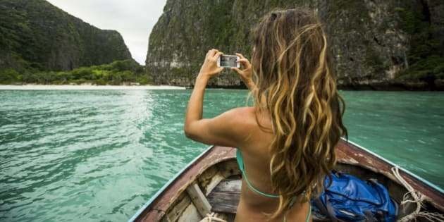 A woman taking a photo while riding on a long tail boat  to a tropical island in Thailand.