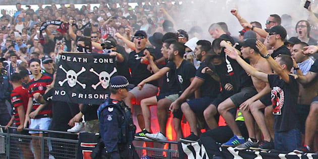 MELBOURNE, AUSTRALIA - FEBRUARY 06:  Wanderers fans in the crowd let off flares as police officers look on during the round 18 A-League match between the Melbourne Victory and Western Sydney Wanderers at Etihad Stadium on February 6, 2016 in Melbourne, Australia.  The FFA (Football Federation Australia) has fined the Western Sydney Wanderers $50,000 and given a suspended three-point A-League deduction after finding the club guilty of bringing the game into disrepute after 25 flares and detonators were set off during the match.  (Photo by Scott Barbour/Getty Images)