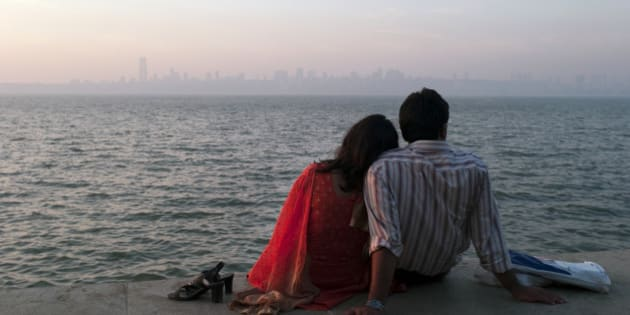An Indian couple enjoy a sunset view from Marine Drive in Mumbai, India.